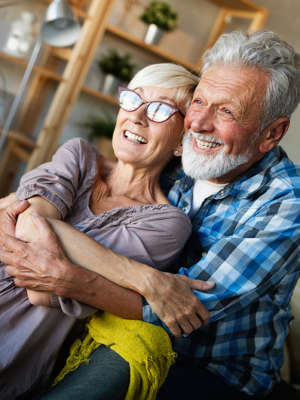 Happy romantic mature couple hugging and enjoying retirement at home